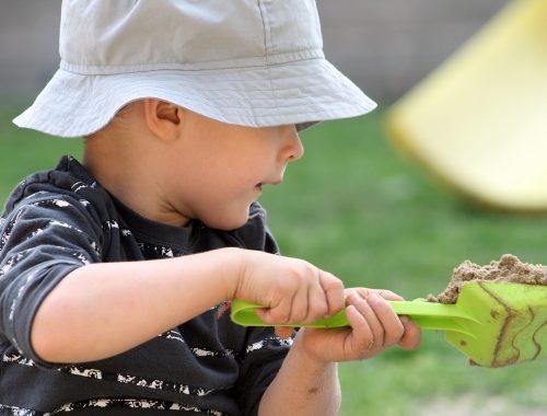 kisfiú homokkal játszik