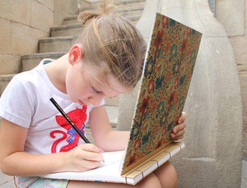 kislány egy füzetbe rajzol