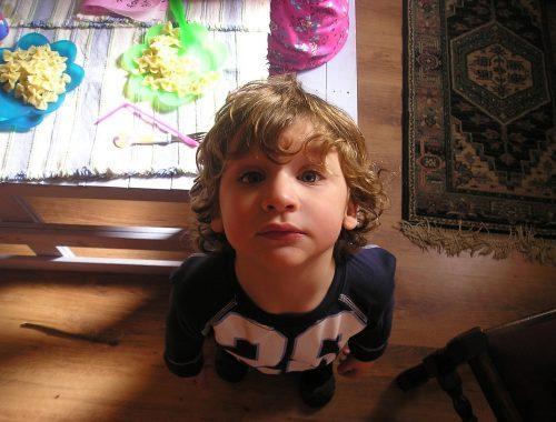 kisfiú áll egy asztal mellett
