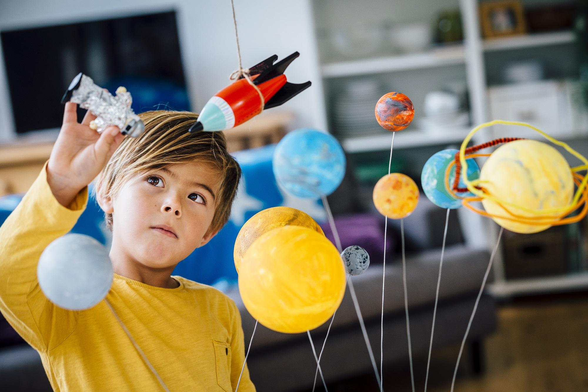 kisfiú űrhajóval és bolygókkal játszik