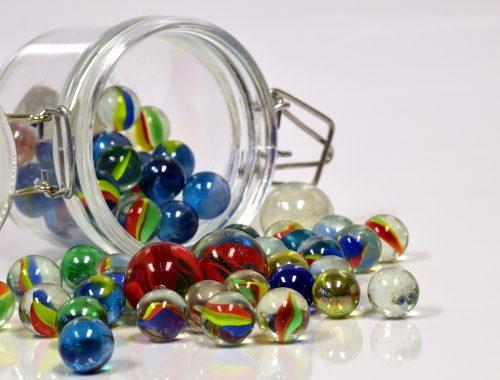 színes üveggolyók kigurulnak egy befőttes üvegből