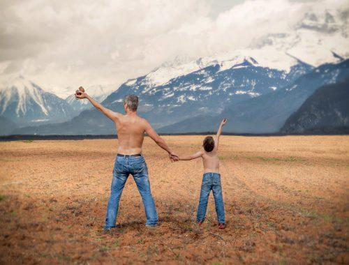 apa és fia egy farmernadrágban állnak a mezőn