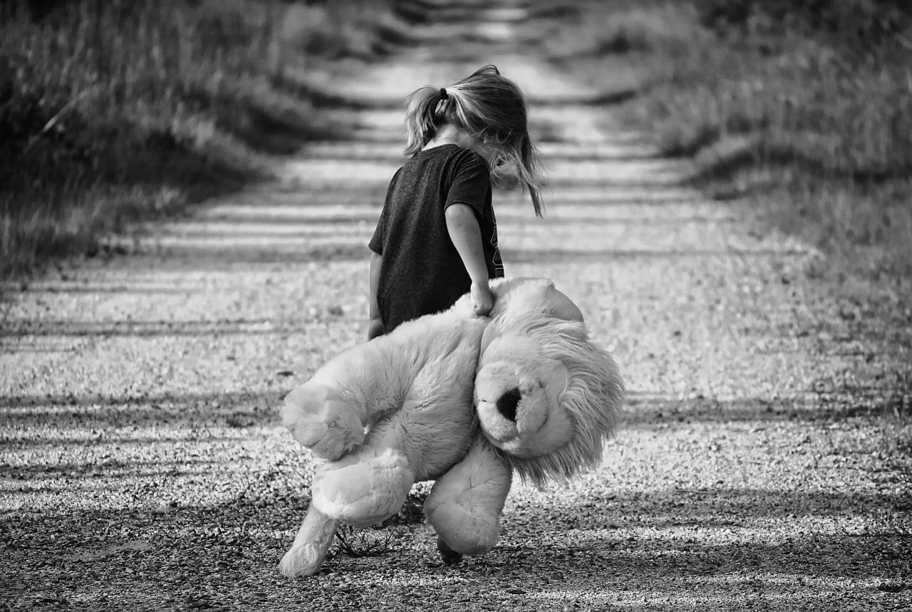 kislány egy játék oroszlánt húz a földön