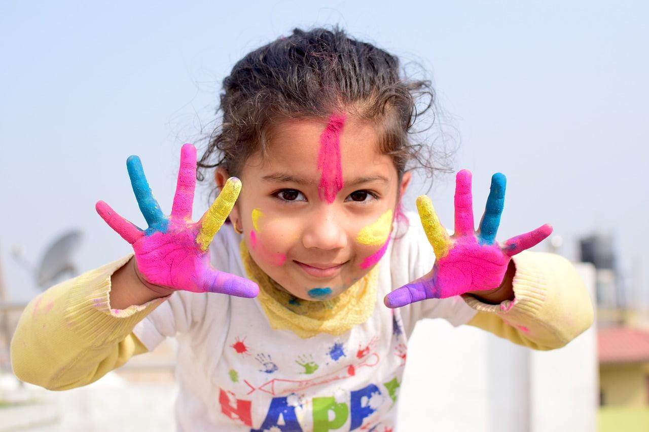 Sokszínű festékkel játszó kislány.