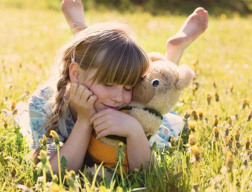 Kislány a réten egy játékmackóval.