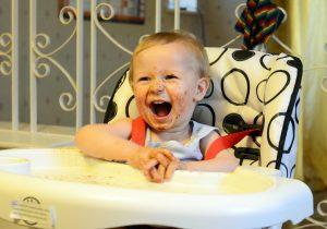 Maszatos kisfiú ül boldogan az etetőszékben.