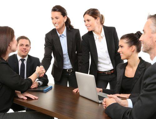 Két nő bemutatkozik a kollégáinak az irodában.