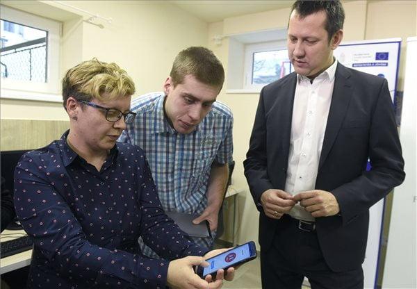 Németh Regina gyógypedagógus bemutatja az autisták mindennapi életét segítő applikációt egy okostelefonon Zörgő Tamás autizmussal élő fiatalembernek az Autizmus Alapítvány Delej utcai épületében 2020. január 28-án. Mellettük Fülöp Attila szociális ügyekért felelős államtitkár (j). MTI/Bruzák Noémi