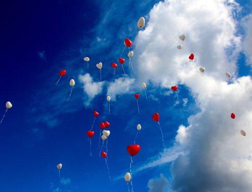 Szív lufik repülnek az égen.