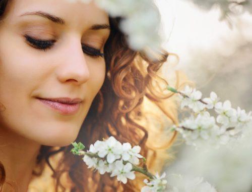 Nő tavaszi virágzó faággal.