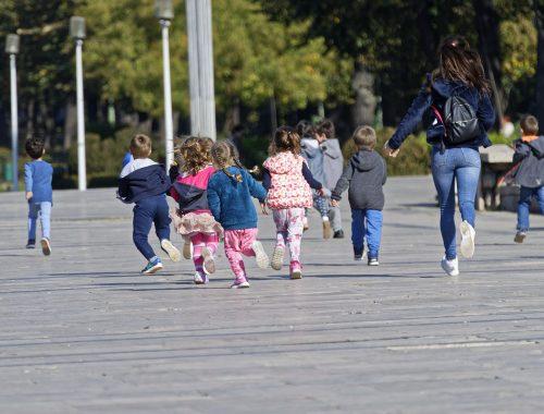 Óvodás gyerekek futnak az óvónővel.