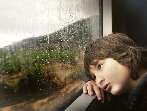 Fáradt gyerek a vonatablakban nézi az esőt.
