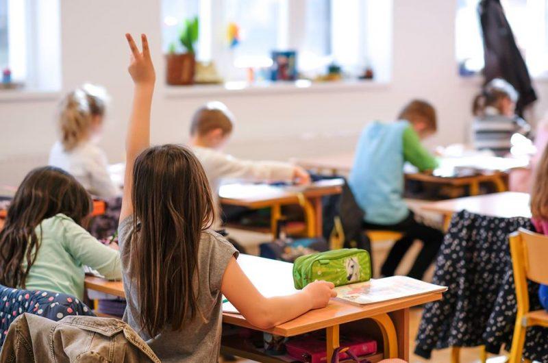 kislány jelentkezik az osztályteremben - óvodai és iskolai jelentkezés